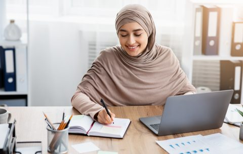 Smiling Islamic Businesswoman Using Laptop And Writing Notes, Managing Her Schedule