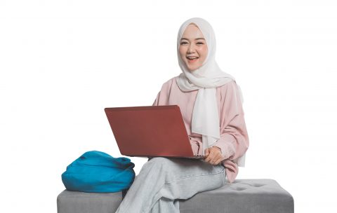 asian muslim student holding laptop in front of white