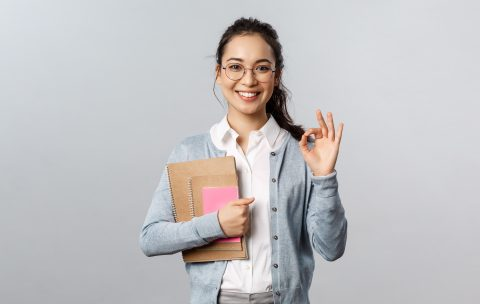 Education, teachers, university and schools concept. Excellent school, join our online lesson. Portrait of satisfied young female student in glasses, show okay sign and hold notebooks with homework